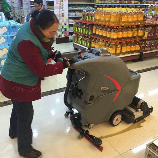 超市保洁人员使用手推式洗地机
