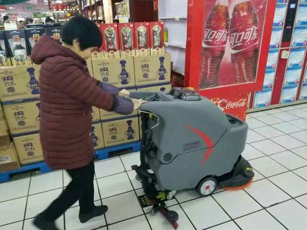 超市保洁员使用全自动洗地机清洁地面